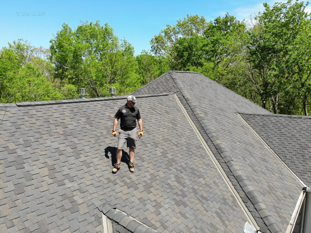 Roofing contractor standing on roof